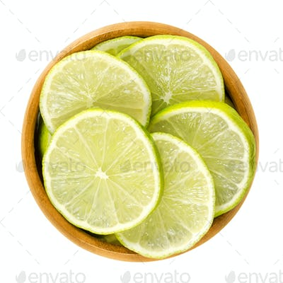 Lime slices in wooden bowl over white