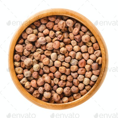 Dried snow pea seeds in wooden bowl