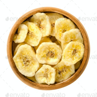 Dried banana chips in wooden bowl over white