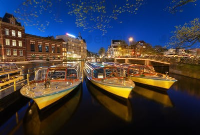 Night cityscape with traditional old houses and boats in Amsterd