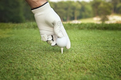 Gloved Hand of Golfer Places Ball on Tee