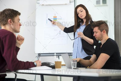 Businesswoman Giving Presentation While Using Laptop With Cowork