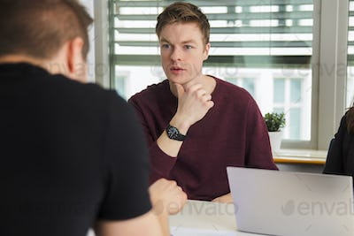 Businessman Communicating With Colleague At Desk