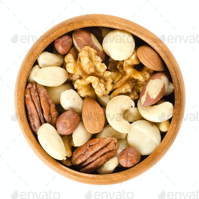 Raw mixed nuts in wooden bowl over white