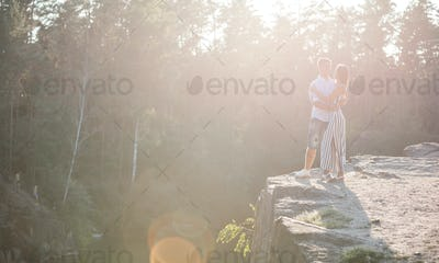 Romantic young couple standing on cliff over river before sunset