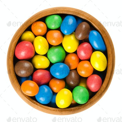 Colorful chocolate peanut candies in wooden bowl over white