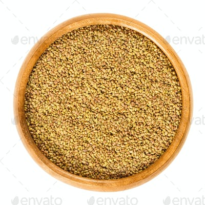 Alfalfa seeds in wooden bowl over white