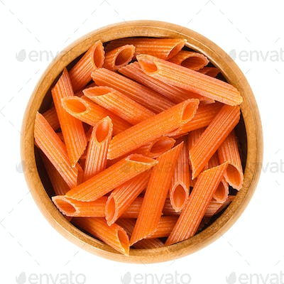 Red lentils penne pasta in wooden bowl over white