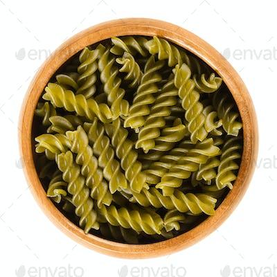 Green peas fusilli pasta in wooden bowl over white