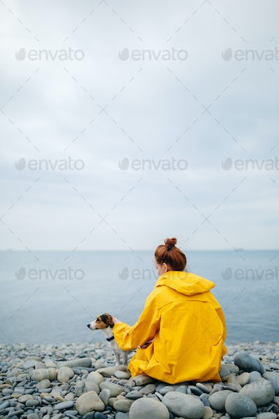 Woman with dog on coast
