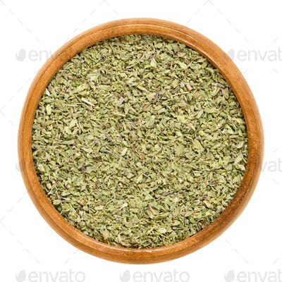 Oregano dried in wooden bowl over white