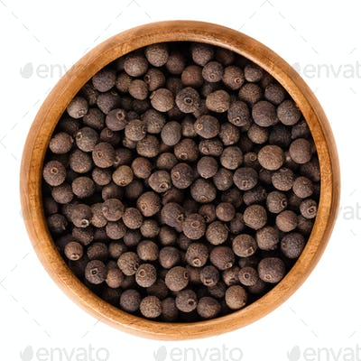Allspice berries in wooden bowl over white