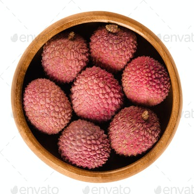 Lychee or litchi fruits in wooden bowl over white