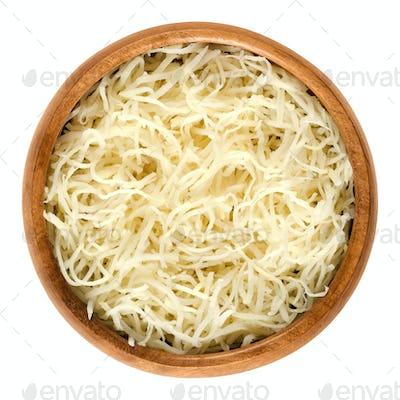 Prepared horseradish in wooden bowl over white