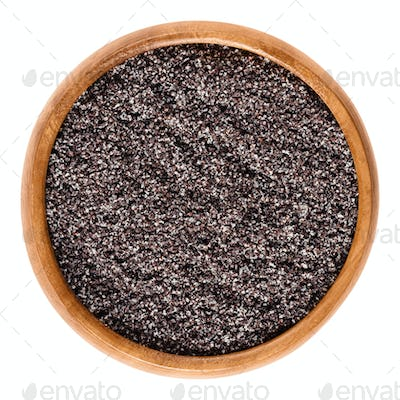 Ground gray poppy seeds in wooden bowl over white