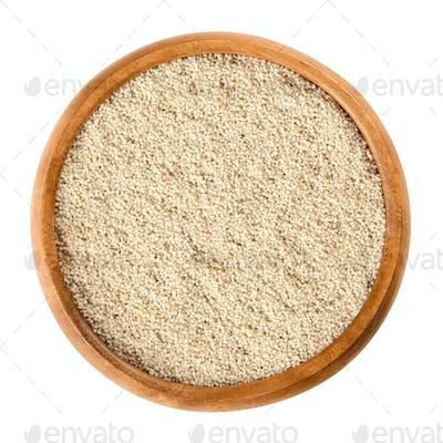 White poppy seeds in wooden bowl over white