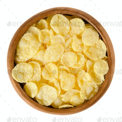 Corn flakes in wooden bowl over white
