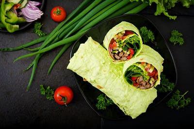 Shawarma from juicy beef, lettuce, tomatoes, cucumbers, paprika and onion in pita bread