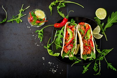 Mexican tacos with chicken fillet in tomato sauce and salsa of paprika and arugula.