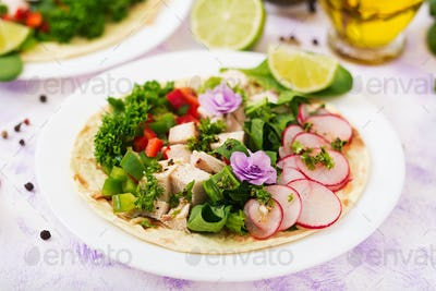 Healthy mexican corn tacos with boiled chicken breast, spinach, radish and paprika.