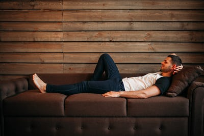 Young happy man lying on couch, relaxation on sofa