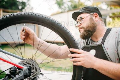 Bicycle mechanic in apron adjusts bike spokes