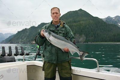 Fisherman in Alaska Holds Up Nice Silver Salmon