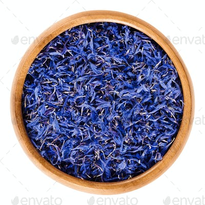Dried cornflowers in wooden bowl over white