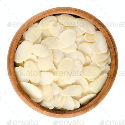 Sliced blanched almonds in wooden bowl over white