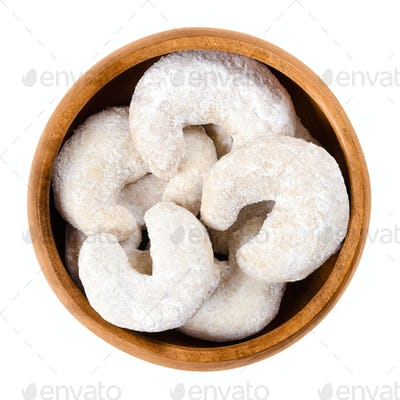 Crescent-shaped vanilla biscuits in wooden bowl over white