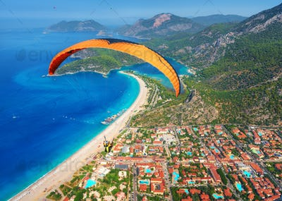 Paraglider tandem flying over the sea with blue water and mounta