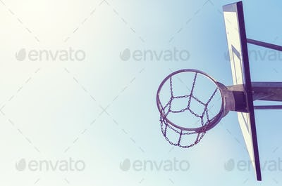 Basketball hoop with chain net at sunset.