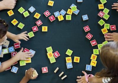 Kindergarten kids playing wooden alphabets letters vocabulary ga