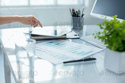 Close-up of female hands using laptop while working on computer at modern office interior