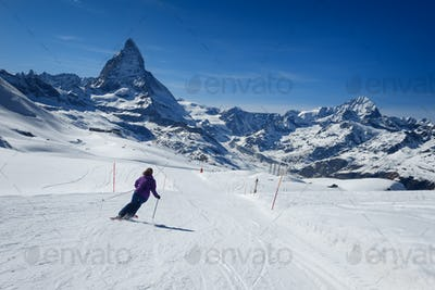 Female skier skiing towards Matterhorn mountain
