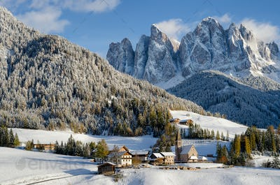 St. Magdalena village in front of Dolomites mountains in the snow
