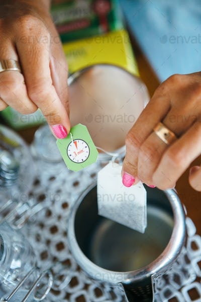Woman putting teabag to cup