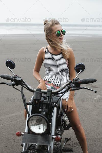 Girl sitting on vintage custom motorcycle