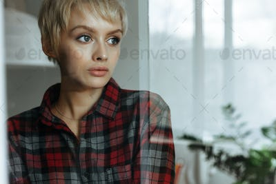 Young woman standing near window