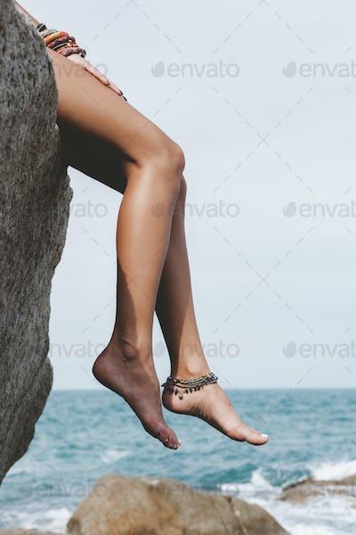 Female legs against the sea