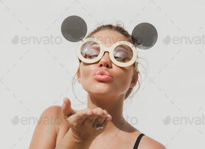 Cute blonde wearing sunglasses and sending a kiss