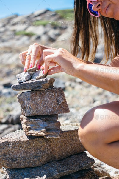 Woman putting stones one upon another