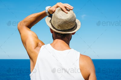 Man holding hat looking at ocean