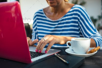 Woman typing laptop and having coffee