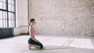 Beautiful yoga girl doing asanas in studio
