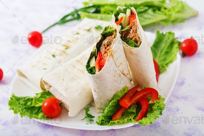 Burritos wraps with minced beef and vegetables on a light background.