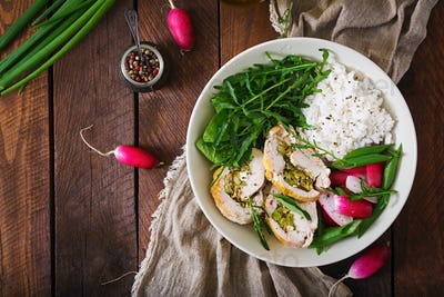 Healthy salad with chicken rolls, radishes, spinach,  arugula and rice