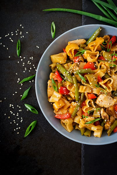 Stir Fry from chicken fillet, green beans and paprika with pasta