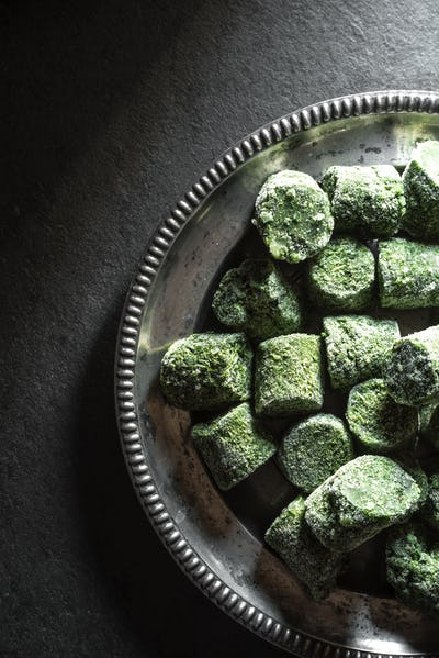 Frozen spinach in briquettes on an old tin plate