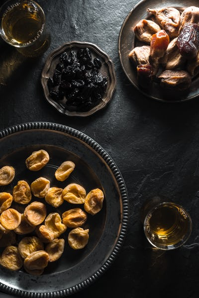 Oriental style tea with dried apricots, dates and raisins on a stone table